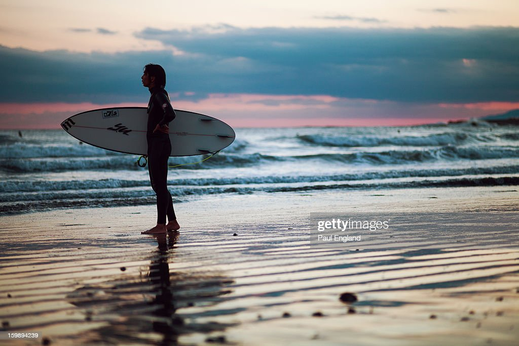 CONTENT] A surfer stands on the beach at sunset in Kamakura