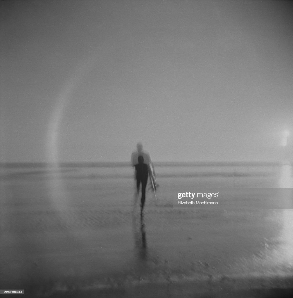 Surfer surrounded by ring of light walks into sea
