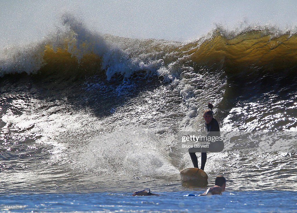 A surfer tries to avoid a collision during four to six foot swells off the Atlantic Ocean on August 28, 2014 in Long Beach, New York. Hurricane Cristobal is churning up larger than normal waves along the eastern coast of the United States.