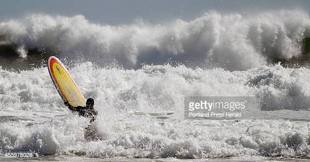 A surfer tries to make his way out to the waves at Higgins Beach in Scarborough Monday September 22 2014