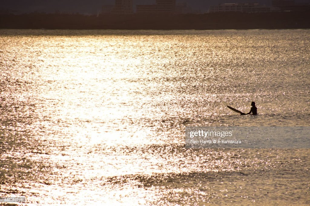 A surfer waiting for next wave on the sunset beach : ストックフォト