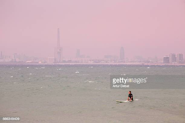 Surfer waiting for the waves in the Barcelona shoreline with the city views Masnou Catalonia Europe