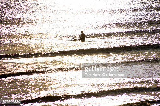 A surfer waiting for wave on the sunset beach : ストックフォト