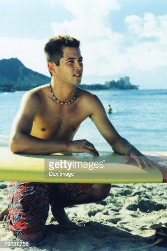 Surfer waiting on beach : Stock Photo
