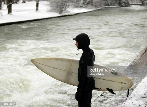 A surfer waits to enter the Eisbach in the English Garden on January 19 2013 in Munich Germany The manmade wave at the Eisbach which has been surfed...