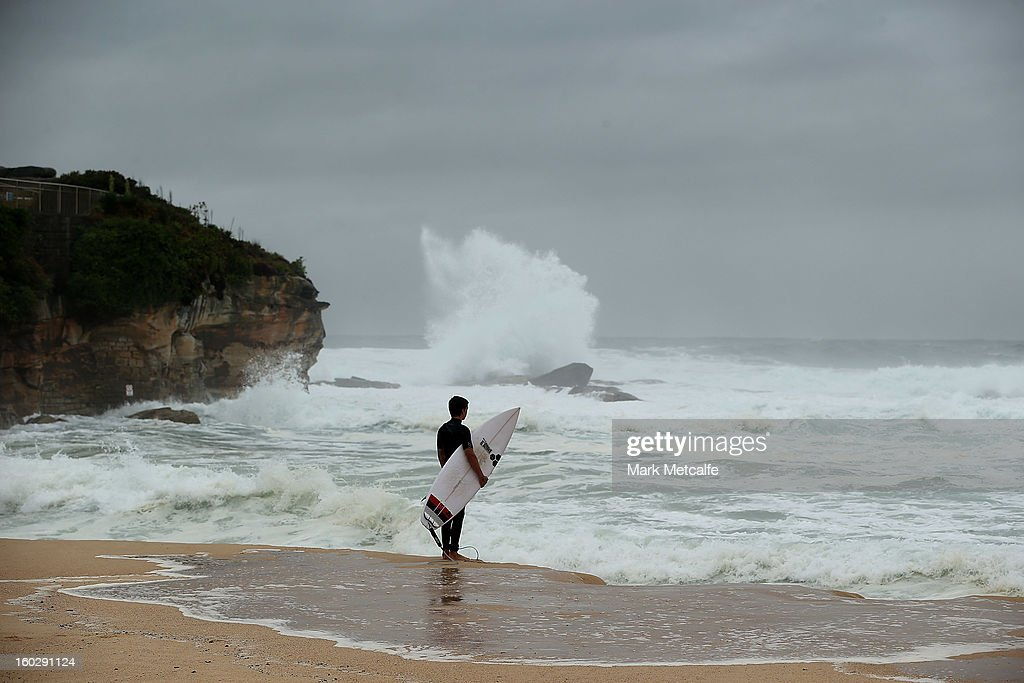 A surfer waits to jump in to the ocean during stormy conditions at Coogee Beach after winds and rain battered Sydney last night on January 29, 2013 in Sydney, Australia. Parts of Sydney are experienced record rainfall after ex-cyclone Oswald swept through the city last night.