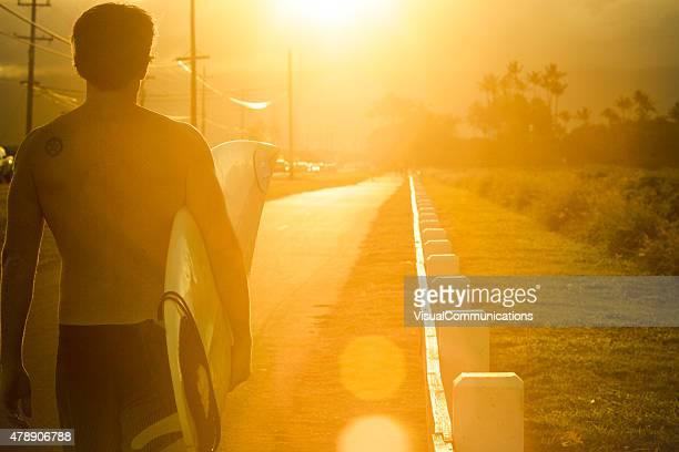 通りを歩くサーファーの夕日をご覧ください。