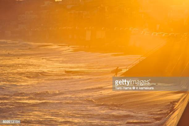 A surfer walking on the sunset beach in Kamakura city in Kanagawa prefecture in Japan