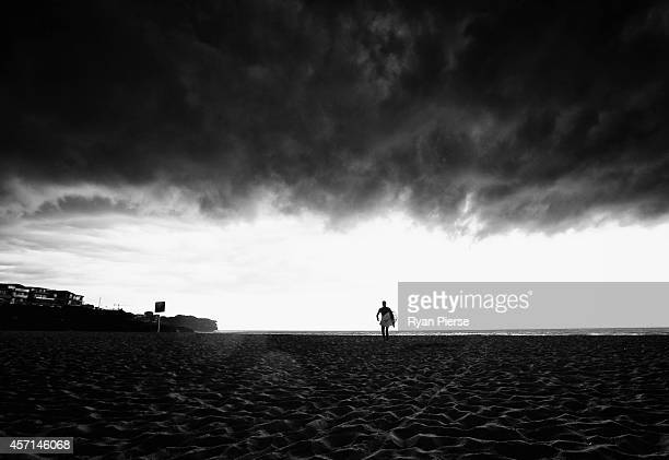 A surfer walks from the water as a severe storm hits Sydney at Bronte Beach on October 13 2014 in Sydney Australia