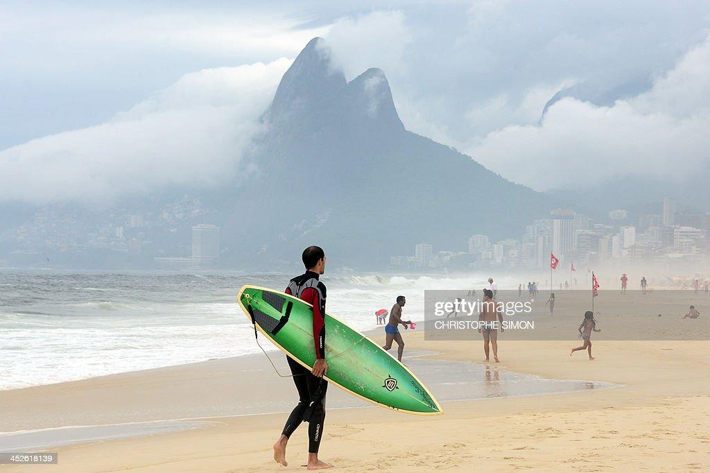 A surfer walks in Ipanema beach on a cloudy day in Rio de Janeiro on November 30 2013 Brazil AFP PHOTO / Christophe Simon