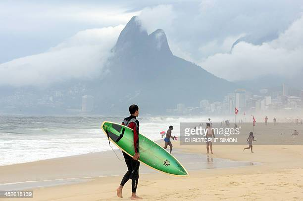 A surfer walks in Ipanema beach on a cloudy day in Rio de Janeiro on November 30 2013 Brazil AFP PHOTO / Christophe Simon