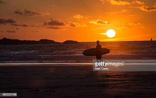 A surfer walks out of the sea as the sun sets at Porthmeor Beach in St Ives on July 29 2015 in Cornwall England After a unsettled start to the school...