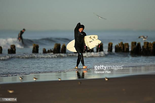 A surfer walks out of the water after an early morning surfing session at Rockaway Beach on July 31 2013 in the Queens borough of New York City...