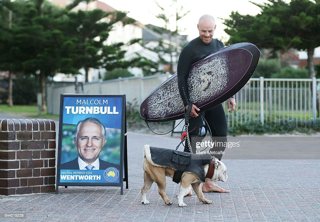 A Surfer walks past an election poster at Bondi Beach in the electorate of Wentworth on July 2, 2016 in Sydney, Australia. Voters head to the polls today to elect the 45th parliament of Australia.