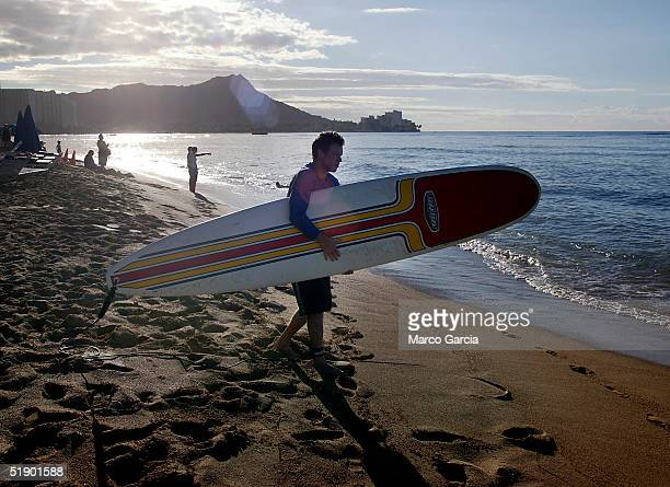 A surfer walks to the water near Waikiki Beach December 29 2004 in Honolulu Hawaii With many of Hawaii's prime hotels condominiums and homes on...