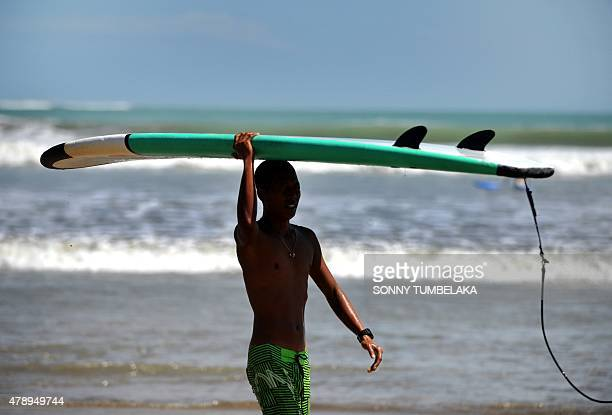 A surfer walks with his board at the beach in Kuta on Bali island on June 29 2015 Surfers are anticipating bigger waves than usual in the coming days...