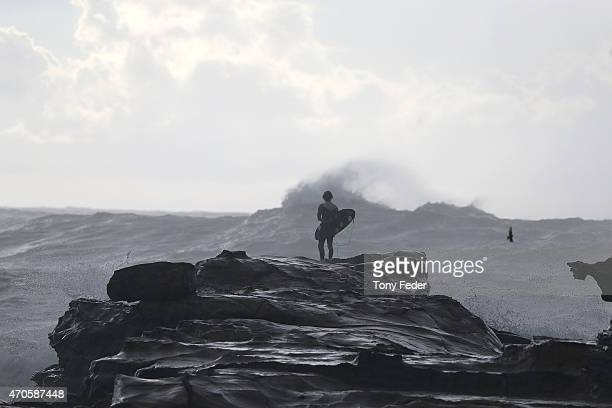 A surfer watches turbulent seas at Avoca Beach on the Central Coast on April 22 2015 in Sydney Australia Three people have died and more than 200000...