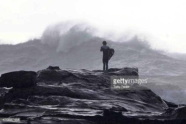 A surfer watches turbulent seas at Avoca Beach on the Cntral Coast on April 22 2015 in Sydney Australia Three people have died and more than 200000...