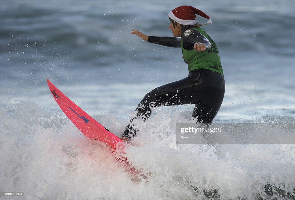 A surfer wearing a Santa Claus hat surfs at Patos Beach, near Vigo, northwestern Spain, on December 23, 2012.