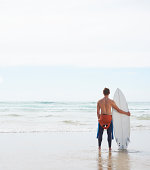 Surfer with board looking out to sea.