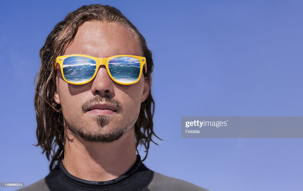 Surfer with sunglasses reflecting waves : Stock Photo