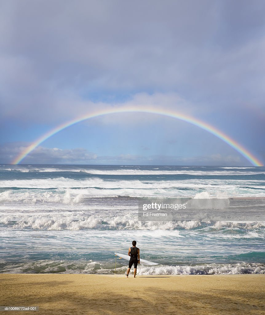 Surfer with surfboard on beach, looking at view : Stock Photo