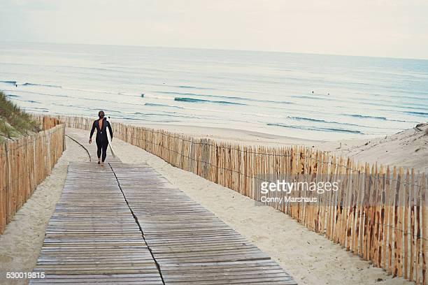 Surfer with surfboard walking to beach, Lacanau, France