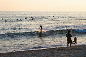 Surfers and fishermen enjoy Sunset on the beach