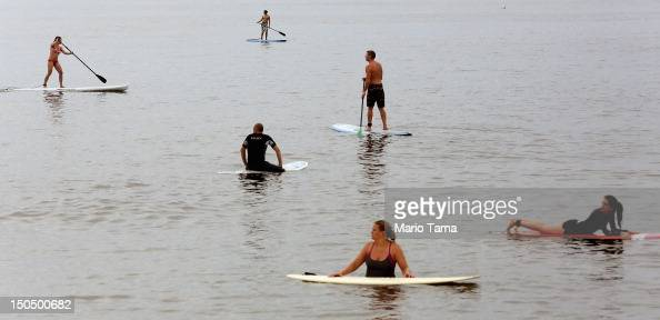 Surfers and paddle boarders gather in the ocean at Rockaway Beach on August 19 2012 in the Queens borough of New York City Over the last few years...