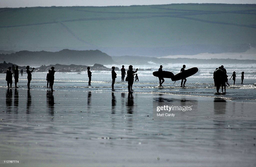 Surfers and swimmers gather at the sea's edge as they enjoy the fine weather in Polzeath near Padstow on April 21 2011 in Cornwall England The UK is...
