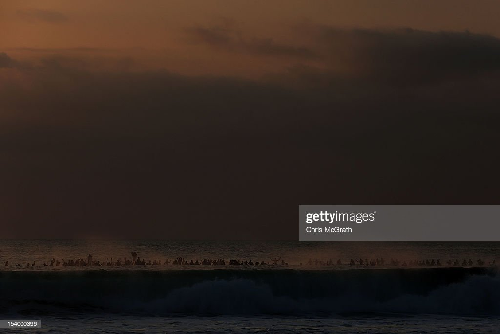 Surfers are covered by the spray from a wave as they form a tribute circle off the beach as part of the Paddle for Peace memorial ceremony on Kuta Beach, Bali, on October 12, 2012 in Indonesia. Hundreds of foreign and local family members, friends and general public gathered at various memorial ceremonies through out the day to remember the victims of the 2002 Kuta nightclub bombings which killed 202 people, including 88 Australians.