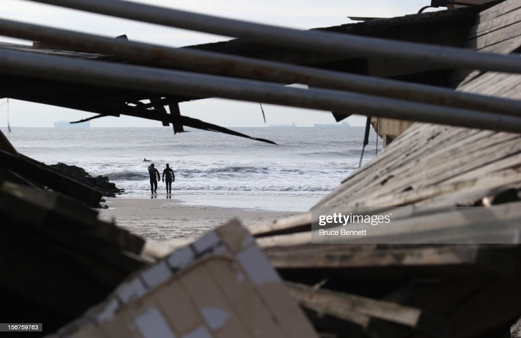 Surfers are framed by the damaged boardwalk on November 20, 2012 in Long Beach, New York. More than three weeks after Superstorm Sandy hit the New York area, residents continue their restoration efforts in many affected areas on Long Island.