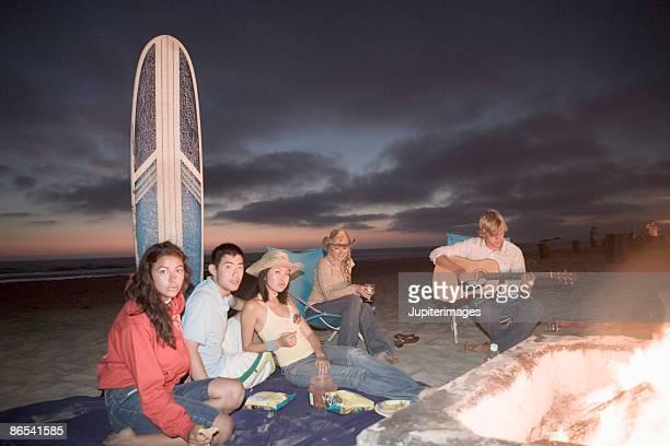 Surfers around beach fire