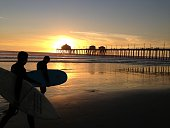 Surfers at sunset in front of the wharf at Huntington Beach California
