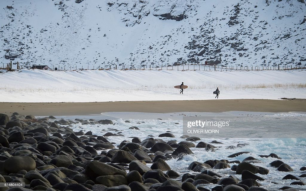 Surfers carrying boards walk at the snowy beach of Unstad, in Lofoten Island, Arctic Circle, on March 10, 2016. Surfers from all over the world comes to Lofoten island to surf in extrem conditions. Ocean temperature is 6-7 °C, air temperature around 0°C in spite of a weather very unstable. / AFP / OLIVIER