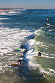Surfers catching waves after memorial paddle out commemorating pro surfer Andy Irons by Huntington Beach Pier.