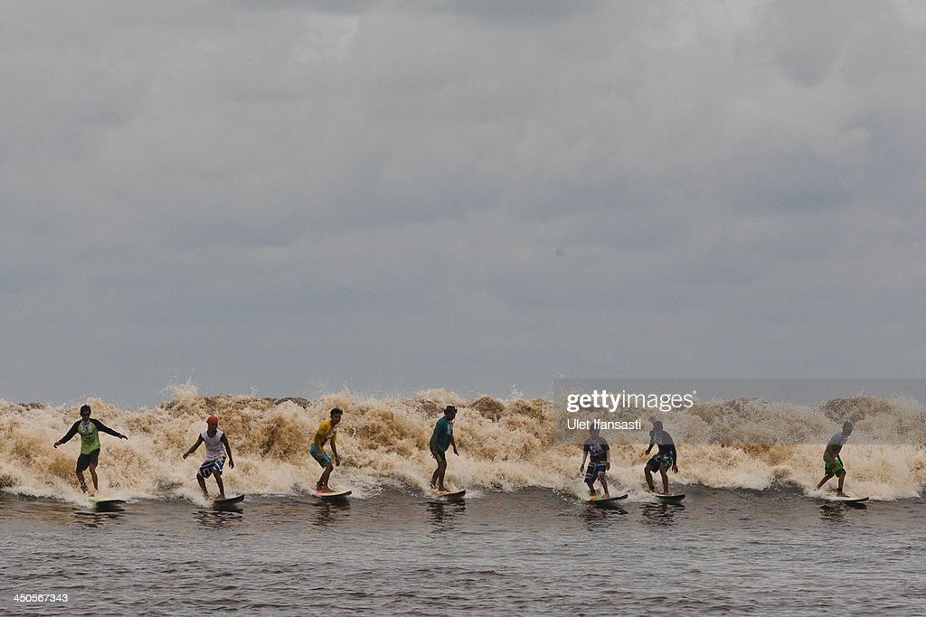 Surfers compete during Bekudo Bono festival at Kampar river on November 19, 2013 in Teluk Meranti village, Riau Province, Sumatra, Indonesia. The Bono tidal wave occurs throughout the year at certain days around the full moon and new moon, however during the rainy season due to the higher volume of water the waves are stronger and bigger. Surfers travel from all over to ride the waves of the Kampar river which can be grow to as high as 10 feet stretching out for more than 50km at times.