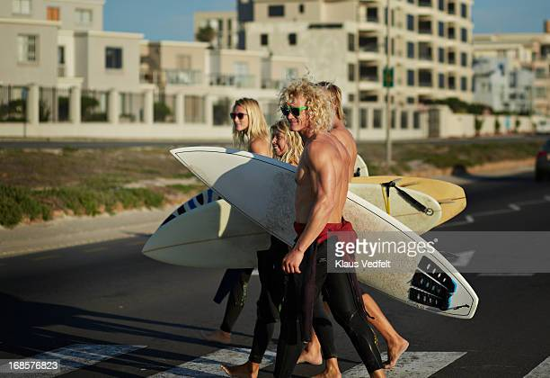 Surfers crossing a road holding their surfboards