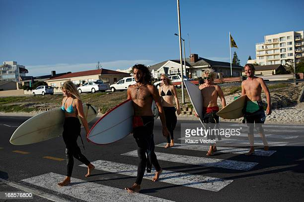 Surfers crossing road on the way to the beach