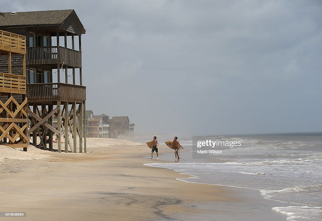 Surfers David Grimes (L) and William Troy walk down the beach while mandatory evacuation orders are in effect for Hatteras Island, July 3, 2014 in Rodanthe, North Carolina. A Hurricane warning has been issued for North Carolina's Outer Banks due to approaching Hurricane Arthur that has been upgraded to a category 2 hurricane.
