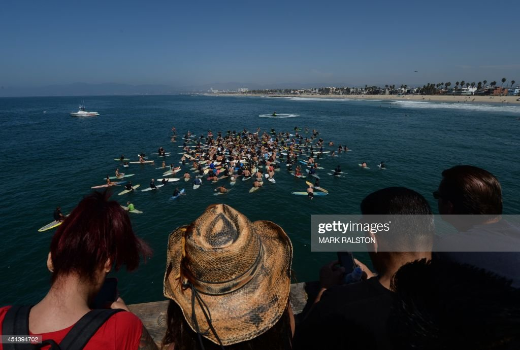 Surfers form a memorial ring during a paddle out as part of the funeral service for the pioneering and legendary skateboarder and surfer Jay Adams who died of a heart attack, at Venice Beach on August 30, 2014. Adams who became famous in the 1970's was an original member of the 'Z-Boy' skateboard team and was portrayed by actor Emile Hirsch in the film ``Lords of Dogtown'', died of a heart attack while vacationing in Mexico. AFP PHOTO/Mark RALSTON