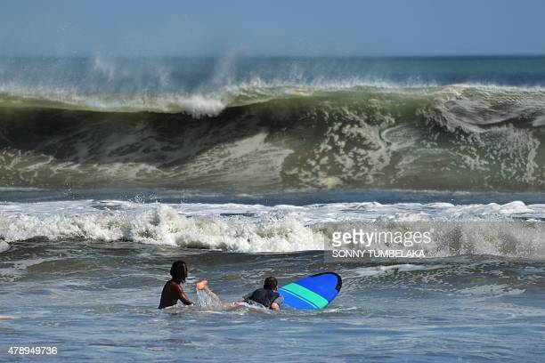 Surfers hit the waves in Kuta on Bali island on June 29 2015 Surfers are anticipating bigger waves than usual in the coming days off the island and...