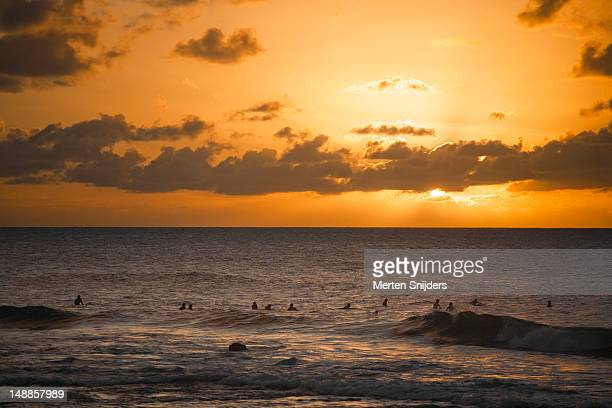 Surfers in line-up at sunset.