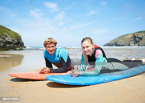 Surfers Laying On Surf Boards At Beach Stock Photo | Getty ...