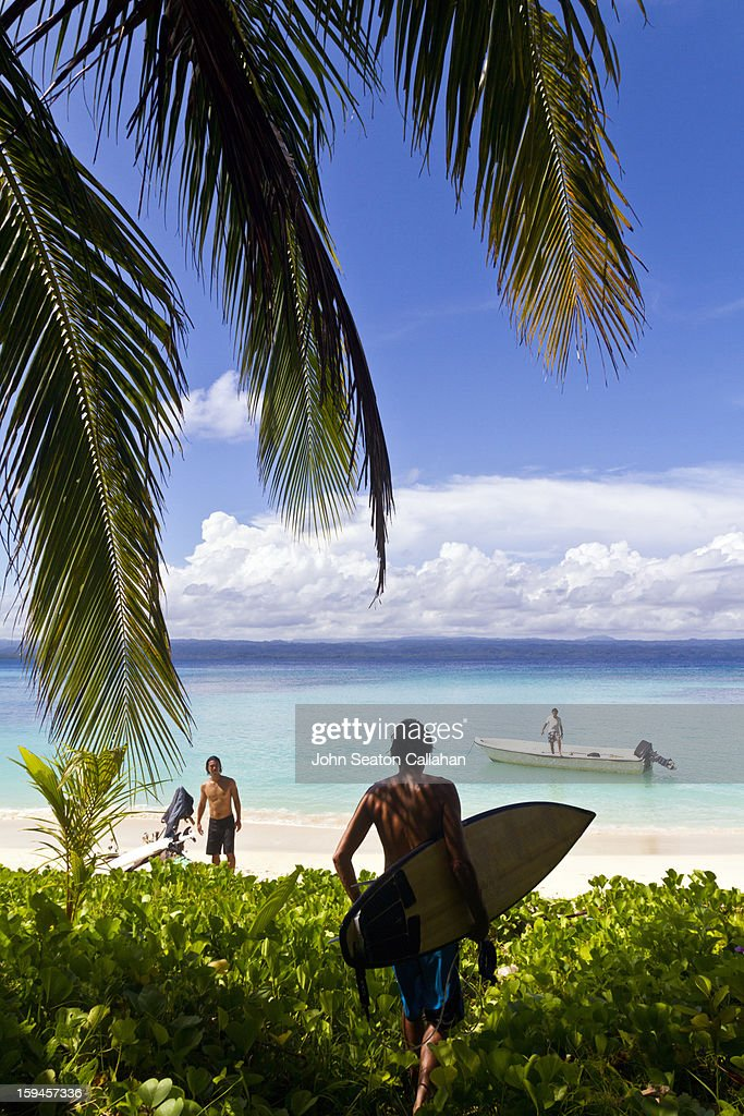 Surfers on offshore island from Halmahera : Stock Photo