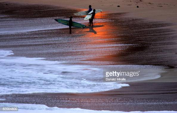 Surfers prepare to enter the water from shore at sunrise during storm surf at Waimea Bay on January 17 2005 in Haleiwa Oahu Hawaii The storm swell...