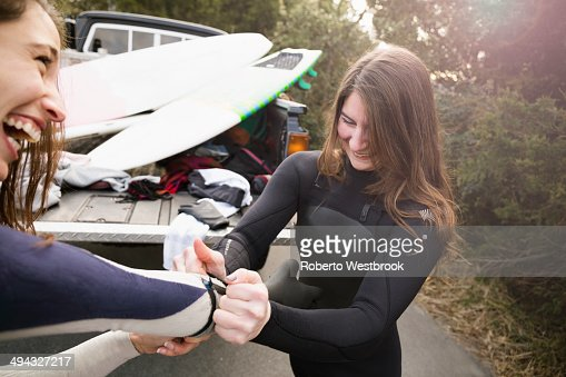 Surfers pulling on wet suits by truck