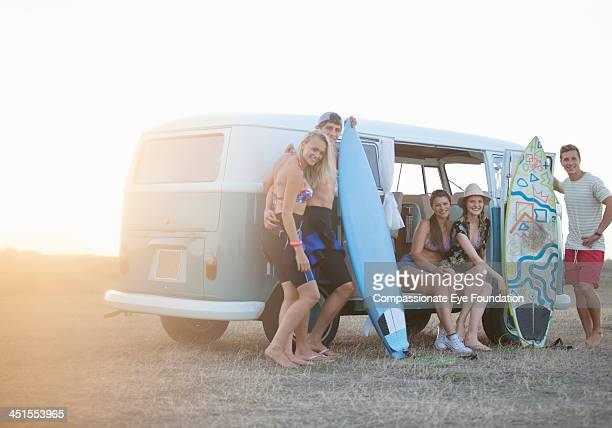 Surfers relaxing by camper van