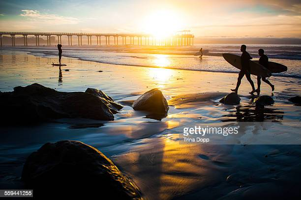 Surfers returning at sunset Scripps Pier La Jolla California 12/03/12