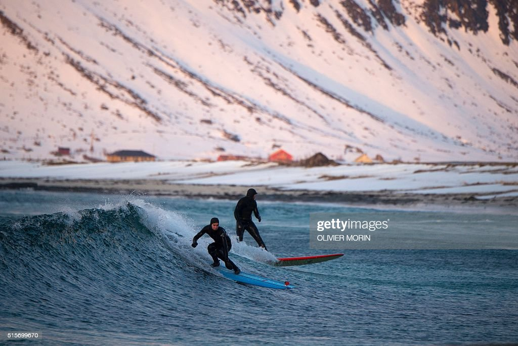 Surfers ride a wave at night time at the snowy beach of Flackstad, in Lofoten Islands, Arctic Circle, on March 12, 2016. Surfers from all over the world come to Lofoten islands to surf in extrem conditions. Ocean temperature is 5-6 °C, air temperature around 0°C in spite of a weather very unstable. / AFP / OLIVIER